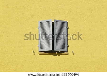 Partly opened gray window shutters on bright yellow wall - stock photo