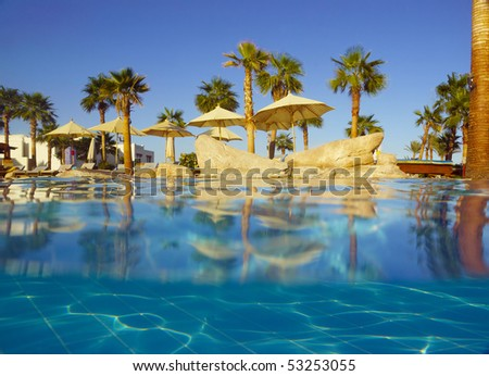 Partly underwater shot from the surface level of the poolside view from the pool - stock photo