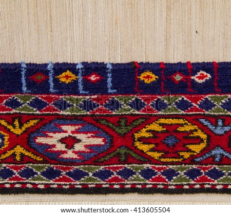 Partly woven carpet, rug on a loom shows wool pile, foundation, warp and weft. Wool is dyed with natural vegetable dyes to create vibrant look. - stock photo