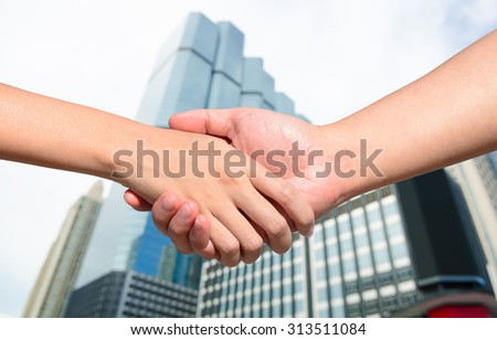 Partner hand between a man and a woman on building background, Teamwork
