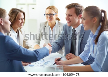 Partners concluding deal and shaking hands in the presence of team members - stock photo