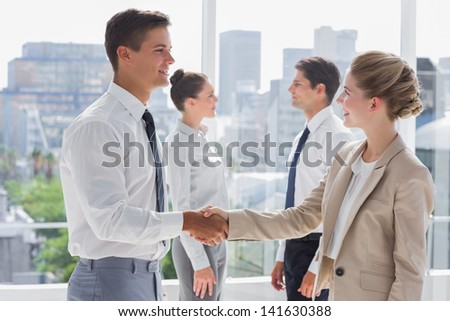 Partners giving a handshake in a bright office