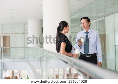 Partners having a conversation in the corridor of a business building - stock photo