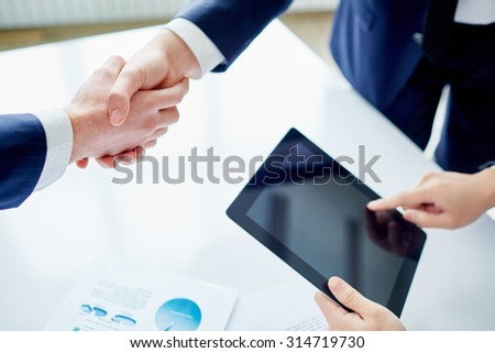 Partners shaking hands while businessman with touchpad networking near by - stock photo
