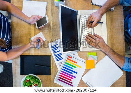 Partners working at desk using laptop and smartphone in the office - stock photo