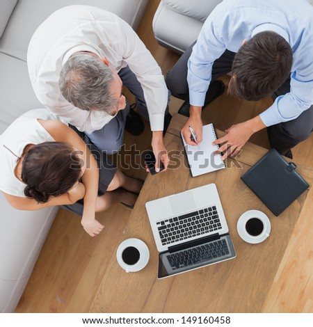 Partners working together and having a coffee in cosy meeting room - stock photo