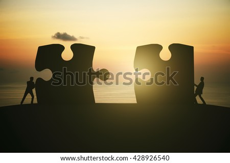 Partnership concept with businesspeople silhouettes putting puzzle pieces together on sunrise background - stock photo
