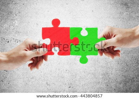 Partnership concept with hands putting green and red puzzle pieces together on concrete backgroud
