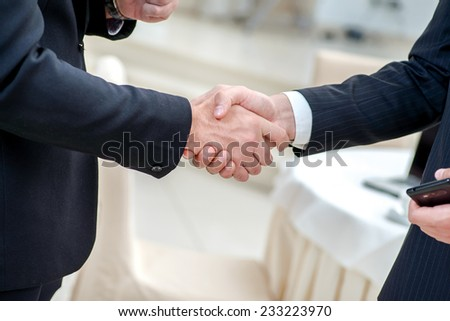 Partnership handshake. Two successful businessman standing in the restaurant and drink coffee while shaking hands with each other close-up view of hands - stock photo