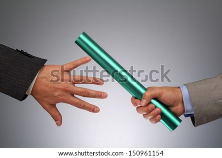 Partnership or teamwork concept two businessmen handing over a baton - stock photo