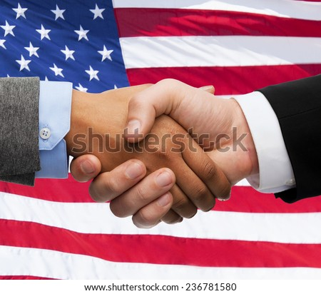 partnership, politics, gesture and people concept - close up of handshake over american national flag background