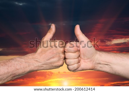 Partnership. Thumbs up sign on sunset sky background - stock photo