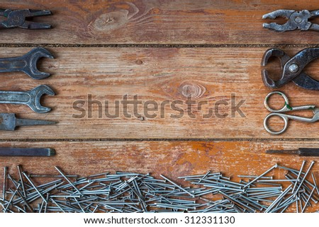 Parts of instruments near pile of shiny nails. - stock photo
