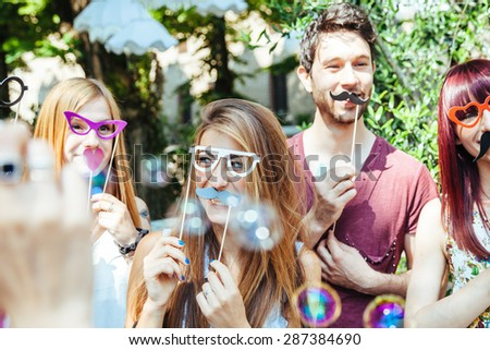 Party! A group of friends, three women and a man have fun at a party in a park with a mustache and fake glasses, joking and talking to each other and playing with soap bubbles in the air! - stock photo