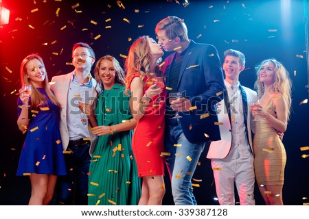 Party and celebration. Couple kissing. Group of seven happy smiling friends having fun together among confetti in night club. - stock photo