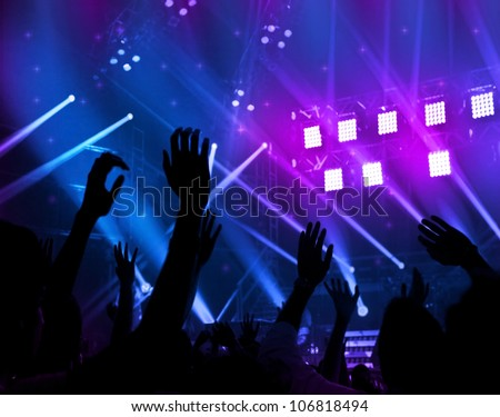 Party background, colorful abstract light, border made of human hands silhouette, happy people jumping large group celebrating new year holiday, men enjoying live band music at night club, fun concept - stock photo