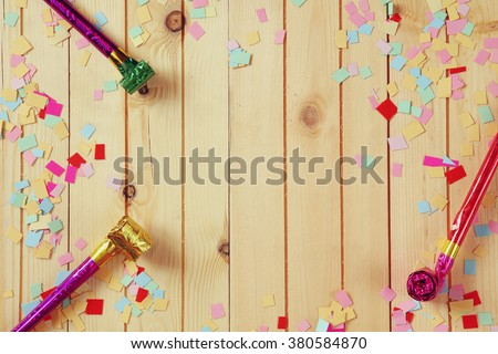 party background with colorful confetti and party whistle - stock photo