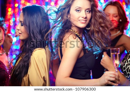 Party being in full swing, pretty girls crowding dance floor - stock photo