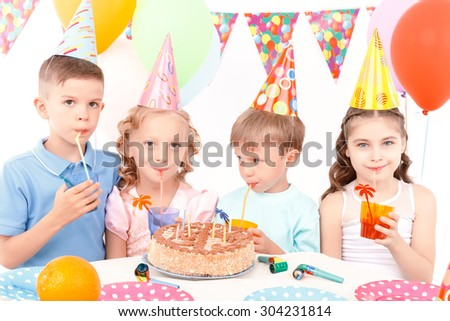 Party beverage. Little cute cheerful children sitting at adorned table with birthday cake and drinking some beverages.
