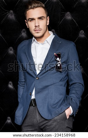 Party boy. Handsome young man in smart casual wear looking at camera while standing against black background  - stock photo