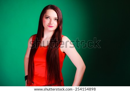Party, celebration and date concept. Attractive young log hair woman in red dress on green background. Studio shot. - stock photo