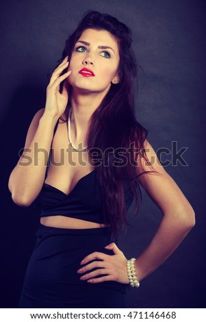 Party celebration concept.  Magnificent long hair woman red lipstick wearing black evening dress pearls necklace on dark