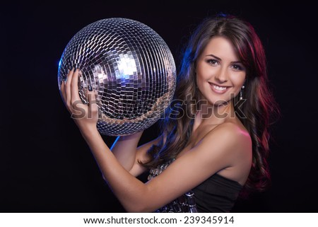 Party, celebration concept. Toned image of beautiful woman in evening dress holding disco ball over black background - stock photo