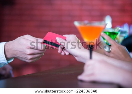 Party, celebration, friends, bachelorette and birthday concept. beautiful womans in evening dresses with cocktails. pay payment card - stock photo