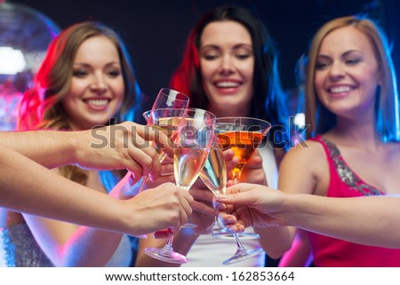 party, celebration, friends, bachelorette and birthday concept - three beautiful woman in evening dresses with cocktails and disco ball