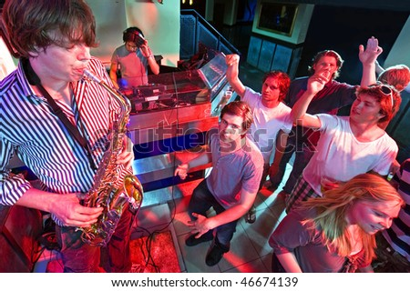 Party crowd going wild during a solo of a saxophonist, accompanied by a DJ - stock photo