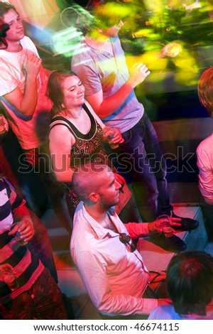 Party crowd on a busy dance floor, engulfed in the lights of a nightclub - stock photo