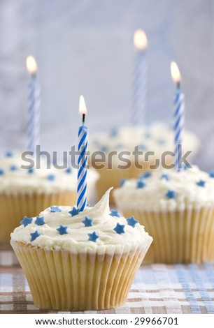 Party cupcakes with lit candles, blue theme - stock photo