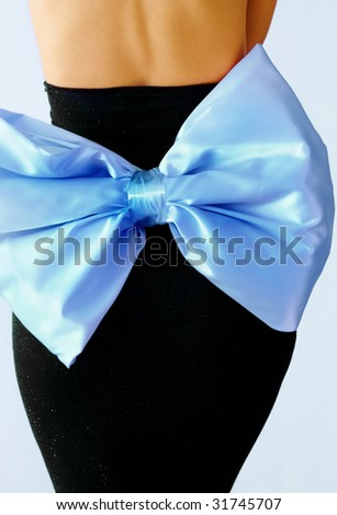 party dress - Back view of black party dress with big blue satin bow - stock photo