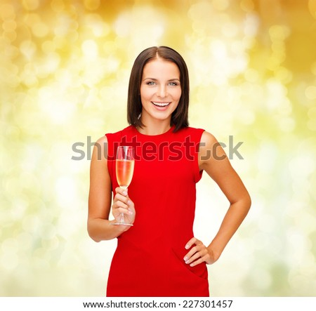party, drinks, holidays, christmas and celebration concept - smiling woman in red dress with glass of sparkling wine over yellow lights background