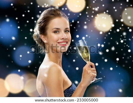 party, drinks, holidays, christmas and people concept - smiling woman in evening dress with glass of sparkling wine over night lights and snow background - stock photo