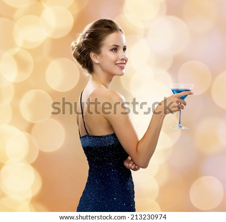 party, drinks, holidays, luxury and celebration concept - smiling woman in evening dress holding cocktail over beige lights background - stock photo