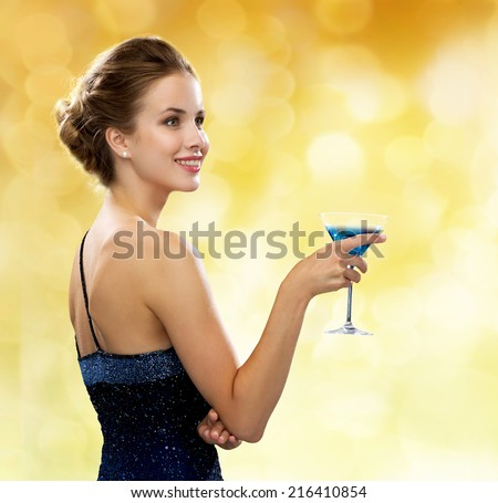party, drinks, holidays, luxury and celebration concept - smiling woman in evening dress holding cocktail over yellow lights background - stock photo