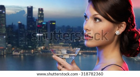 party, drinks, holidays, luxury and celebration concept - smiling woman in evening dress holding cocktail over night city background - stock photo