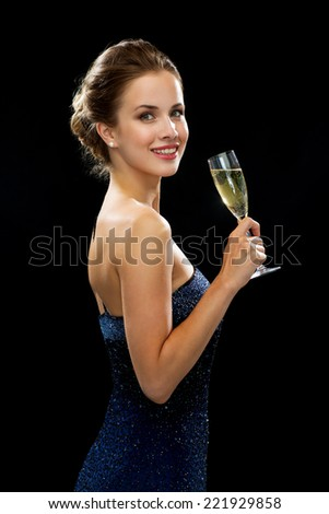 party, drinks, holidays, luxury and celebration concept - smiling woman in evening dress with glass of sparkling wine over black background - stock photo