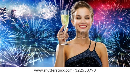 party, drinks, holidays, luxury and celebration concept - smiling woman in evening dress with glass of sparkling wine over nigh city and firework background - stock photo