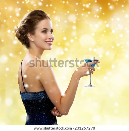 party, drinks, holidays, people and christmas concept - smiling woman in evening dress holding cocktail over yellow lights and snow background - stock photo