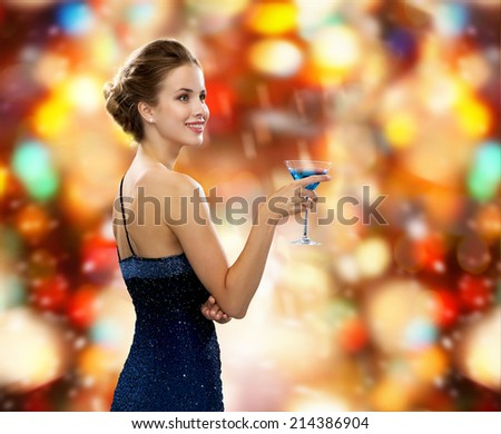 party, drinks, winter holidays, luxury and celebration concept - smiling woman in evening dress holding cocktail over red christmas lights background - stock photo