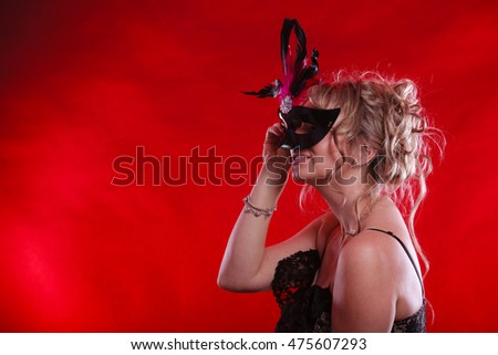 Party entertainment time concept. Woman with carnival mask. Lady wearing elegant blak dress, she has blonde hair.