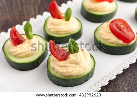 Party finger food cucumber with salmon dip, tomato and basil.
