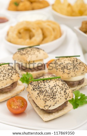 Party Food - Mini cheeseburgers, onion rings, potato wedges, breaded mushrooms and popcorn chicken with chili sauce and sour cream and chives dip. - stock photo