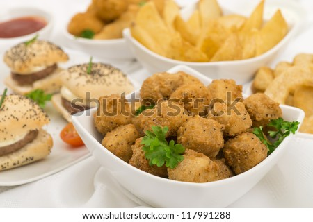 Party Food - Popcorn chicken, mini cheeseburgers,  potato wedges, onion rings and breaded mushrooms with chili sauce and sour cream and chives dip. - stock photo