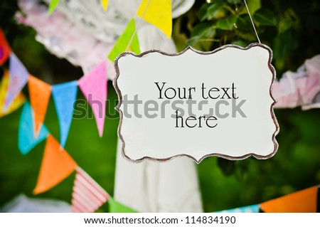 Party garland and empty board with space for text against green trees - stock photo