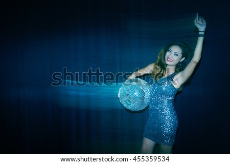 Party girl with disco ball dancing in the dark - stock photo