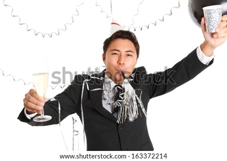 Party guy with glass and mug wearing a suit and tie, party hat and party horn blower. White background. - stock photo