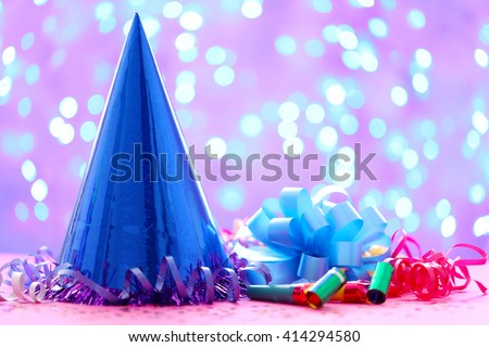 Party hat and other stuff on blurred garland background - stock photo